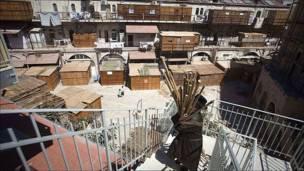"""Un judío ultraortodoxo lleva cañas de bambú para la construcción de una """"sucá"""" en Jerusalén, una construcción termporal para la festividad de Sucot."""