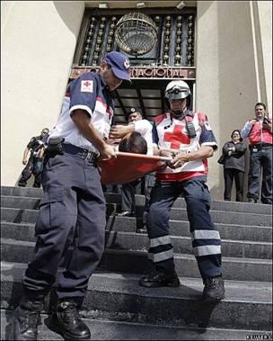 Miembros de la Cruz Roja abandonan el edificio de la Lotería Nacional en Ciudad de México en el marco de un simulacro de evacuación.
