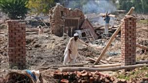 Группа мужчин на развалинах дома