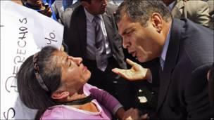 El presidente Rafael Correa habla con una mujer.