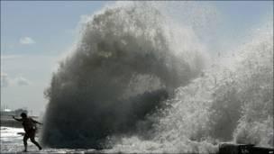 Una mujer corre frente a una enorme ola en la localidad rusa de Sochi, en el mar Negro.