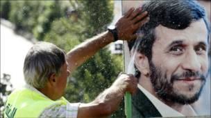 Ливанец со шлангом перед портретом Ахмадинежада