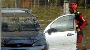 Пожарник стоит у затопленной машины