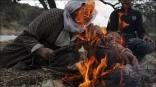 Женщина разводит костер в Хевроне
