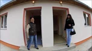 Две женщины стоят перед новым домом