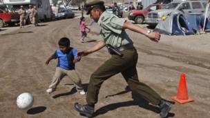 Полицейский играет в футбол с ребенком в лагере спасателей