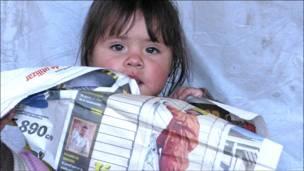 Niña mordisquea un periódico (Fotos y textos Macarena Gagliardi)
