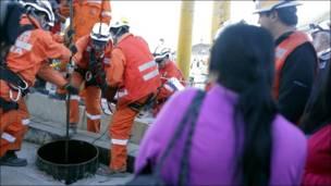 Спасатели поднимают капсулу с шахтером