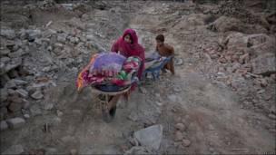 Dos niños caminan por una ruta llena de piedras