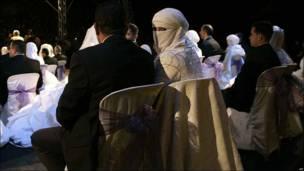 Una novia palestina con el rostro cubierto voltea a la cámara