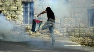Joven palestino huye de las bombas lacrimógenas.
