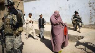Mujer afgana con soldados y niños