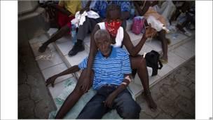 Mujer sostiene a un hombre enfermo en Haití