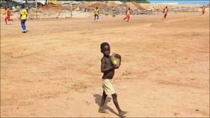طفل يحمل فاكهة جوز الهند