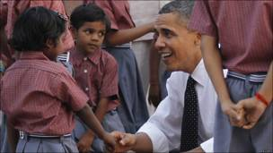 Obama saluda a los hijos de los trabajadores que participan en la restauración de edificios históricos.