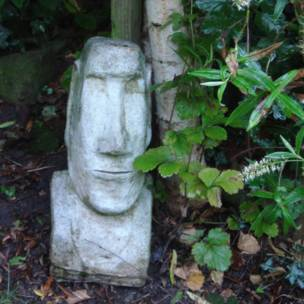 un moái decora un jardín