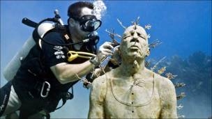 Un submarinista junto a una escultura debajo del mar