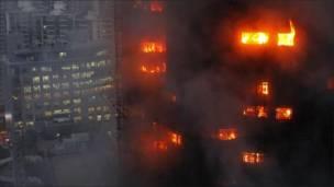 В окнах горящего здания в Шанхае видно пламя