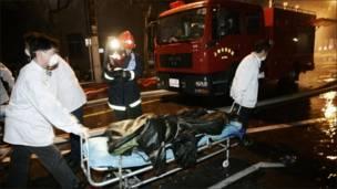 Работники скорой помощи увозят тело погибшего в пожаре в Шанхае