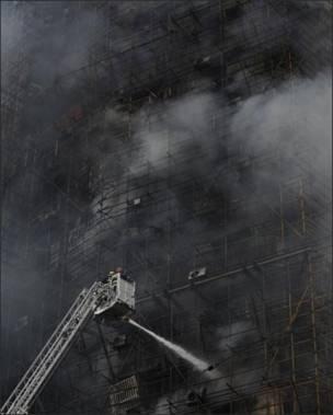 Пожарные тушат горящее здание, окруженное строительными лесами