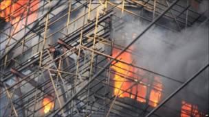 Люди на строительных лесах горящего здания в Шанхае