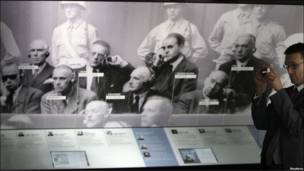 Visitante frente a la foto de los nazi acusados