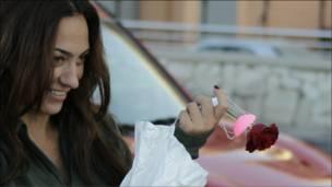 فتاة لبنانية تحمل زهرة حمراء في يوم الاستقلال