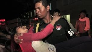 Полицйеский выносит с места трагедии девушку