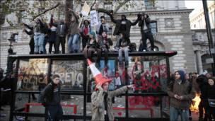 Демонстранты залезли на автобусную остановку, бросают заградительные конусы