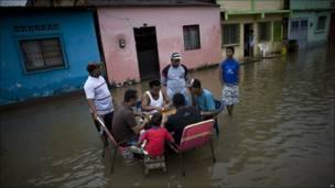 En medio de la inundación, juegan dominó