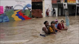 مجموعة من السكان تقف في أحد الشوارع التي غمرتها مياه الفيضانات في كولمبيا