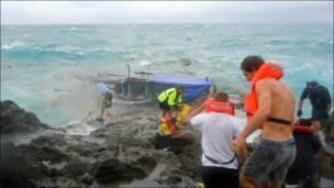 Спасатели достают из воды потерпевших кораблекрушение на острове Рождества