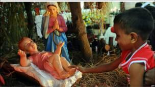 Ноги дитини Ісуса привернули увагу і цього хлопця, який прийшов на різдвяну месу в Коломбо, Шрі Ланка.