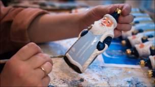 Художница расписывает фигурку Деда Мороза