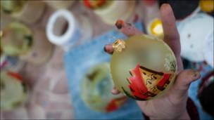 Художница держит елочный шар