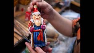 Художница держит фигурку Деда Мороза