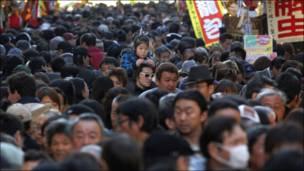 طفلة يابانية تنظر للزحام من على كتف والدها في سوق شعبي مزدحم في طوكيو
