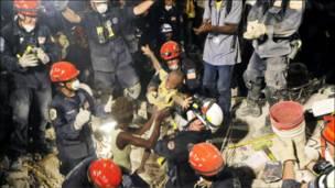 تصویری از یک کودک که توسط امدادگران از زیر آوار بیرون می آید