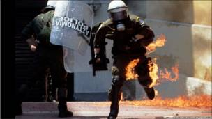 تصویر یک پلیس ضد شورش یونان که آتش گرفته است