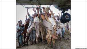 تصویری از سیل زدگان پاکستان که از هلی کوپتر کمک رسانی آویخته اند