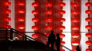 صينيون يسيرون بالقرب من فوانيس مضاءة قبيل بدء الاحتفالات برأس السنة
