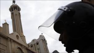 رجل أمن مصري يقف في حالة استعداد خارج الكنيسة المستهدفة
