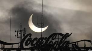 Відчуття театру: цей знімок затемнення крізь вивіску Кока-Коли зроблено в польській столиці Варшаві.