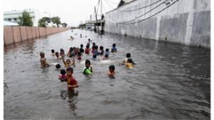 أطفال يسبحون في مياه الفيضانات التي غمرت الشوارع أمام منازلهم في موارا بارو شمال جاكرتا