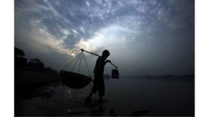 بائع خضار يسير في نهر براهمابوترا في مدينة جوهاتي في الهند.