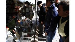 تونسيون ينظرون إلى كتب معروضة في واجهة إحدى المكتبات في تونس
