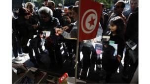 تونسيون ينظرون إلى كتب معروضة في واجهة إحدى المكتبات بتونس