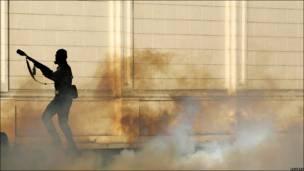 Полицейский с гранатой со слезоточивым газом
