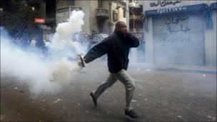 Демонстрант с гранатой со слезоточивым газом