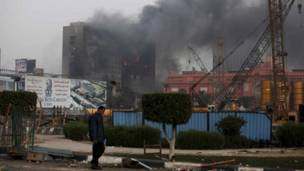 لافتة لموقع فندق ريتز قرب مبنى المتحف المصري بجوار مقر قيادة الحزب الحاكم المحترق